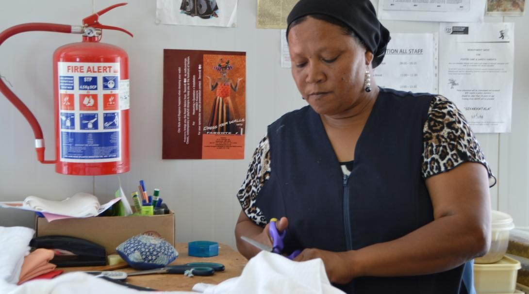 Female International Development Intern cuts with scissors through material during her work placement in South Africa.